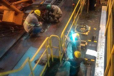 Trabalhadores em uma planta de fabrica implementando sistema hidráulica
