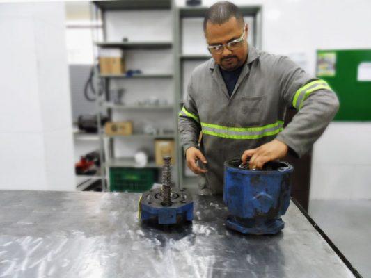 Profissional dispondo peças de uma bomba hidráulica